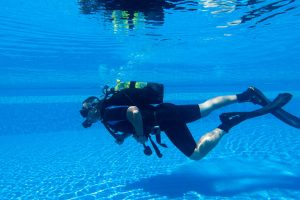 Is Scuba Diving Hard? Man learning how to scuba dive in a pool.