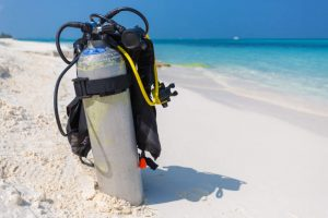 How Does Scuba Diving Work? Scuba diving equipment sitting on the beach.